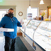 Pedro Rias, of Goshen, purchases a box of pastries Monday morning at Dutch Maid Bakery in Goshen.