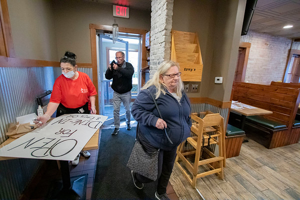 """Tony's Famous Grill server Renee Chesterfield, left, creates a sign saying """"Open for dine-in and carry out"""" while Mike Pierce and his wife Anne Pierce, enter to dine in at Tony's Famous Grill in Goshen. Monday is the first day that dine in service is permitted at 50% capacity in restaurants in Indiana."""