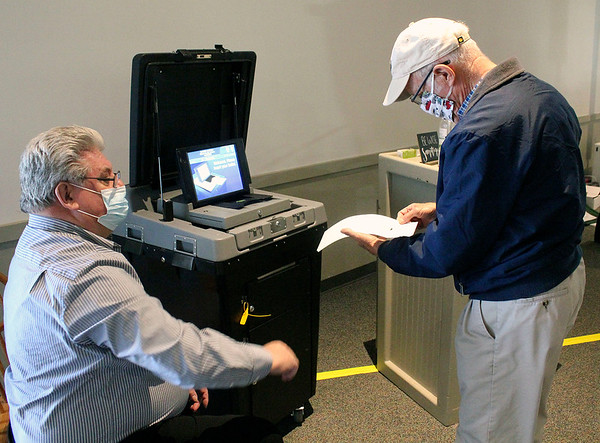 Roger Schneider | The Goshen News<br /> Donald Detweiler of Goshen checks his ballot before depositing it into the ballot box manned by poll worker David Boroff at Maple City Chapel.