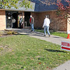 Roger Schneider | The Goshen News<br /> Poll worker Glenn Null holds a door open for voters Tuesday morning at the Greene Road Church vote center.
