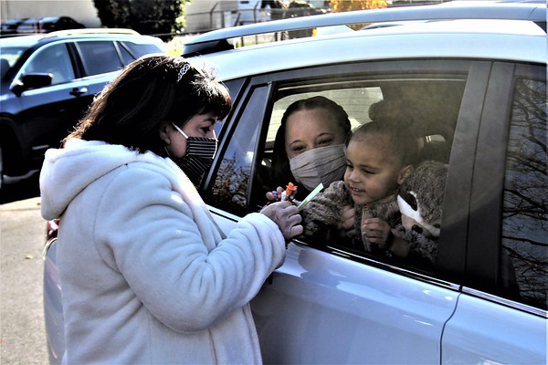 John Kline | The Goshen News<br /> Laurie Marks, of the Middlebury Breakfast Optimist Club, left, hands out treats to 2-year-old Reina Weaver, right, as her mother, Maria Weaver, holds her during a Trunk or Treat drive-through event at the Middlebury Community Public Library Saturday morning.