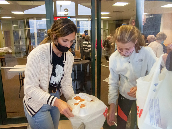 Monica Lehman and Claira Foust package meals for customers during Saturdays The Window Haystack Fundraiser at Grace Community Church in Goshen.