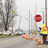 TCS flagger Kim Davis, right, holds a temporary stop sign while Northern Indiana Public Service Company crews work on putting in new power lines in Saturday at the intersection of County Road 38 and County Road 31 in Goshen.