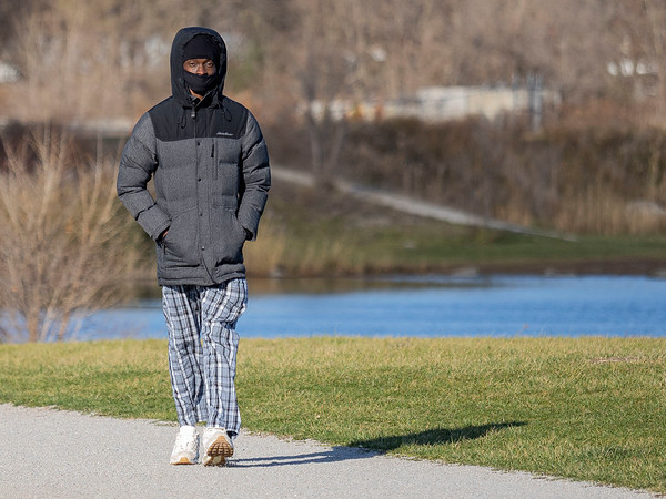 Eric Barnes, of Fort Wayne, takes a brisk walk along the trail at Fidler Pond Tuesday afternoon in Goshen.