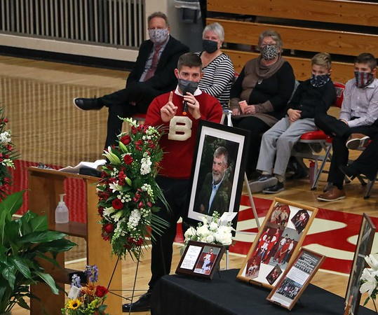 Colin Dechant gives a speech about his father, former Goshen High School wrestling coach John Dechant, during the celebration of life ceremony for John Wednesday at Goshen High School. John was also a history teacher, Dean of Students and Athletic Director at various times while at GHS. John passed away on Oct. 15 in Syracuse. Colin is wearing his dad's old varsity football sweater from when John played at Ball State University. About 200 people attended the celebration in person, and the event was also streamed online for those who couldn't make it.