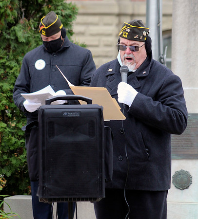 Roger Schneider | The Goshen News<br /> Goshen Veterans of Foreign Wars post commander George Buckmaster conducts the Veterans Day ceremony Wednesday while VFW chaplain John Alheim stands in the background.