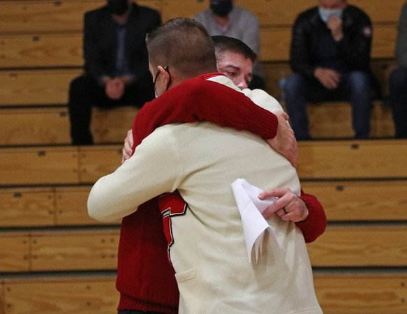 Shawn Dechant, white sweater, and Colin Dechant hug after Colin's speech about their father, John, at John's celebration of life service Wednesday at Goshen High School.