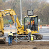 Phend and Brown heavy equipment operator Derek Custer uses an excavator with labors Josh Lambert and Erik Aspinwall  to work on shoulder Thursday at the newly opened roundabout at U.S. Highway 6 and Indiana State Road 13 in Benton.