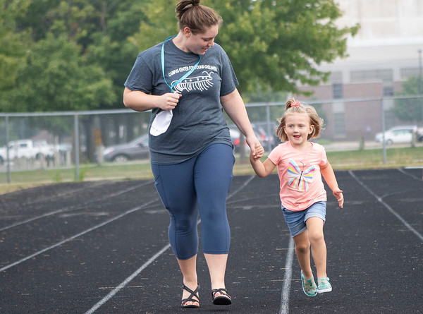 Campus Center for Young Children Lead Teacher Jenna Mikel, left, runs with Everly Ehret, Tuesday morning on the track at Goshen College Eigsti Track and Field Complex. Students were on their daily walk around campus to get some exercise.