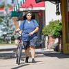 Whitney Roach, of Goshen, walks with her bike along the sidewalk of North Main Street Friday in Goshen.