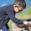 Mateo Horta, 4, of Goshen, plays with a spiderweb on a park bench Friday at Fidler Pond in Goshen.