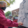 Abstract Artist Thomas Zuber, of Osceola, paints an abstract piece of artwork Saturday along Main Street in Goshen.