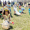 Mikera Walker, 4, Elkhart, places her eggs in a bag as other Easter egg hunters scour the field for 3- and 4-year-olds at Grace Community Church in Goshen Sunday afternoon.