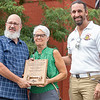 """City of Goshen Mayor Jeremy Stutsman, right, presents the """"Good of Goshen Award to Electric Brew Owners Myron and Dana Bontrager Friday in downtown Goshen. The Electric Brew has been serving the Goshen community for 25 years."""