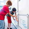 Ethan Sloan, left, helps Caleb Beam place his restroom edict board on the white board Monday during the first day of school at Goshen Intermediate School.