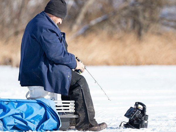 An ice fisherman sits on a bucket while ice fishing on Fish Lake Tuesday afternoon in the 10,000 Block of County Road 34 in Goshen