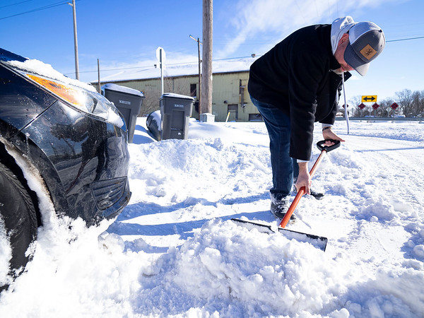 Kevin Long, of Goshen, shovels out his car after getting stuck in his driveway Tuesday morning in the 500 block of East Douglas Street in Goshen.
