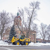 """City of Goshen Street Department heavy equipment operator Ron Pollock uses a front loader with a 3 1/4 yard bucket attachment Thursday afternoon to clear parking spaces along East Lincoln Avenue in front of the Elkhart County Courthouse in Goshen. Pollock said, """"Clean up is going to continue through tomorrow into next week."""""""