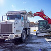 A bobcat operator loads a Quality Excavating truck with snow Tuesday morning in the parking lot of The Oasis in Goshen.