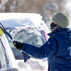 Kristin Saner, of Goshen, uses a snow brush to clear off her  vehicle Tuesday morning in the 500 block of East Purl Street in Goshen.