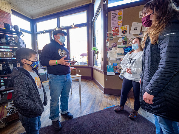 Caleb Gunawan, 8, left, and his father Martin, left rear, both of Goshen, offer to pay for drinks for Aubrey Miller, of Goshen, right rear, and AnneMarie Bell, of Elkhart, right front, who visited the Electric Brew Tuesday afternoon.