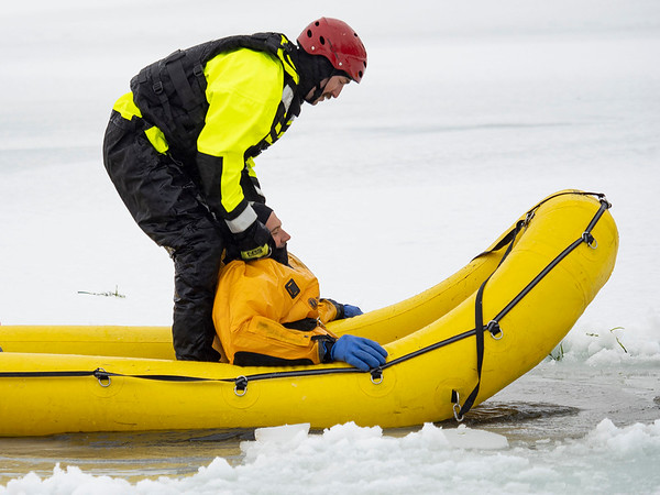 Goshen firefighter  private Kyle Stamm, left, prepares to lift firefighter Lt. Phil Schrock from the frozen pond Monday morning at Shanklin Park during an ice rescue training session in Goshen.