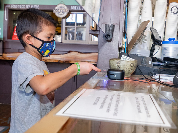 Caleb Gunawan, 8, of Goshen, pays for several drink orders for customers who visited the Electric Brew Tuesday afternoon.