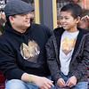 Caleb Gunawan, 8, right, and his father Martin, talk while sitting on a bench outside the Electric Brew Tuesday afternoon in Goshen.