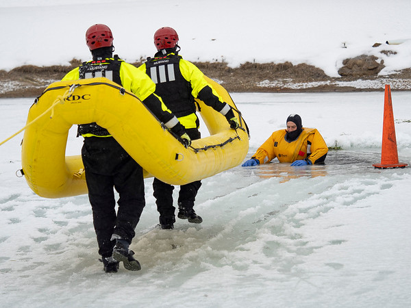 Goshen firefighters  private Kyle Stamm, and Sgt. Erik Crisp deploy an RDC to rescue firefighter Lt. Phil Schrock from the frozen pond Monday morning at Shanklin Park during an ice rescue training session in Goshen.
