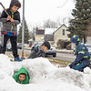 Trae Reeves, 10, left front, MJ Reeves, 7, left rear, Daniel Ramirez, 9, and  Mason Honeycutt, 9, right, all of Goshen, play on a snow bank in the parking lot of Parkside Elementary Tuesday afternoon in Goshen.