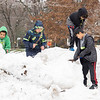 Trae Reeves, 10, left, Mason Honeycutt, 9, left middle, Daniel Ramirez, 9, right front, and MJ Reeves, 7, all of Goshen, play on a snow bank in the parking lot of Parkside Elementary Tuesday afternoon in Goshen.