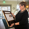 Dutch Maid Bakery employee Connie Kramer, looks over a plaque she received from Dutch Maid Bakery President and CEO Lyle Miller Thursday during an open house at Dutch Maid Bakery located at 508 W. Lincoln Ave. in Goshen. Krammer is retiring after 56 years of service at Dutch Maid Bakery. The plaque showcases an article commemorating her 50th work anniversary.