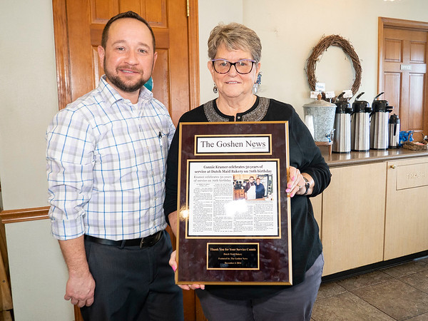 Dutch Maid Bakery President and CEO Lyle Miller, left, presents long term employee of 56 years Connie Kramer with a plaque Thursday during an open house at Dutch Maid Bakery located at 508 W. Lincoln Ave. in Goshen. The plaque showcases an article commemorating her 50th work anniversary.