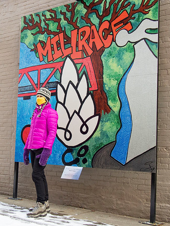 """Mim Shirk, of Goshen, observes the """"Windows"""" mural by Leah Cassidy Borden Thursday afternoon while she stands in front of the """"For the Love of the Millrace"""" mural by Josh Cooper in an East West alley between Edward Jones Investments and Sorg Jewlers along South Main Street in Goshen."""