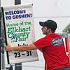 Alajos Sefcsik, who works for Signtech, hangs a banner announcing the dates of the Elkahrt County 4-H Fair on a lamp post along Lincoln Avenue in Goshen Wednesday. The fair begins three weeks from today.