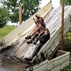 John Kline | The Goshen News<br /> Participants brace for a muddy splash while sliding down one of the many obstacles encountered during the annual Mudtastic Classic in Syracuse Saturday morning.