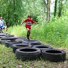 John Kline | The Goshen News<br /> Participants work their way through a tire run during the Mudtastic Classic in Syracuse Saturday morning.