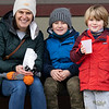 Leah Richardson, left, and her sons Max Richardson, 7, and Luke Richardson, 4, all go Goshen, enjoy sider and doughnuts on a park bench Saturday during the Downtown Goshen Fire and Ice Festival along Main Street in Goshen.