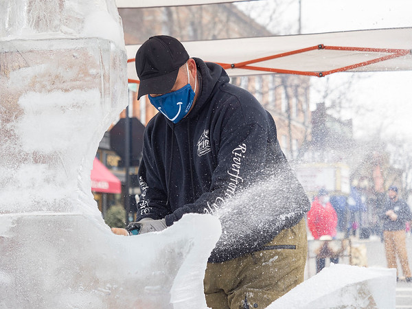 Ice Carver Jim Houser carves an ice sculpture in front of spectators Saturday during the Downtown Goshen Fire and Ice Festival along Main Street in Goshen.