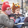 Bre Daugherty, left and her Daughter Elona Daugherty, both of Goshen, watch Ice Carver Patrick Hunsley, of Michigan City, carve an angle fish Saturday during the Downtown Goshen Fire and Ice Festival along Main Street in Goshen.