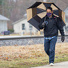 Goshen College Spanish Professor Cris Garza walks with an umbrella Thursday morning along the Ninth Street entrance of Goshen College in Goshen. Rain and wind dominated the day ahead of an expected sunny and warmer weekend.