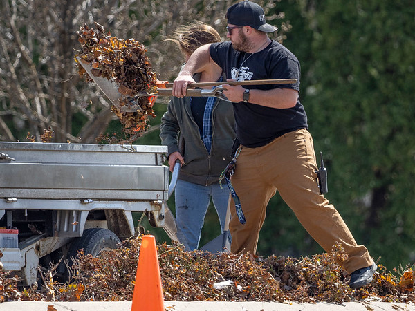 Greencroft Communities employee Jakob Hostetler uses a rake and shovel to collect leaves Tuesday near the entrance of Greencroft Communities at the intersection of College Avenue and Greencroft Boulevard in Goshen.