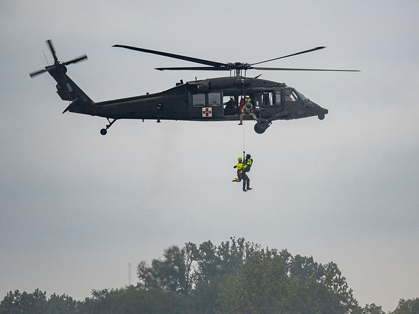 The Indiana Army National Guard pilots a VH60L helicopter during the U.S. Army's Indiana Helicopter Aquatic Rescue Tream training exercise at Fiddler Pond Wednesday in Goshen. The rescuer's name is Rescue Technician Steve Pritz who is holding onto the cable and the rescued personal from the helicopter.