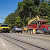 Traffic flows through a work site along College Avenue Thursday morning near the intersection of College Avenue and U.S. 33 in Goshen. A Phend & Brown heavy equipment operator uses an excavator to load the truck with dirt to make head way for an additional lane along College Avenue.