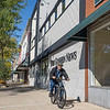 A cyclist rides his bike along the side walk on South Main Street in front of The Goshen News building Friday afternoon.