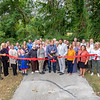 Chip Van Vurst, center with scissors, cuts the ribbon during the ribbon cutting ceremony and grand opening of the The Ashley Van Vurst Sensory Trail Tuesday at Abshire Park in Goshen.