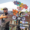 Local artist Josh Cooper showcases a piece of art during the Arts on the Millrace 2021 event along the Millrace Canal in Goshen.