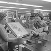 "THE GOSHEN NEWS | APRIL 16, 1980<br /> It was National Library Week and the Goshen Public Library celebrated with a week of activities. Pictured, Karen Moore Beltler, 1321 S. Eighth St. at right, checks out a painting by artist Jerzy Titled ""Fuchsia"" The Library offered about 200 framed reproductions for check-out. Paintings were checked out six weeks at a time."