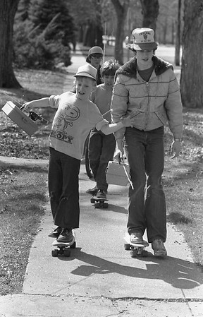 THE GOSHEN NEWS | APRIL 9, 1983<br /> The sunny and warm weather Friday encouraged many area residents to venture outside for entertainment and recreation. These four Bristol youths used available transportation of skateboards and a bicycle to travel to the St. Joseph River for a  day of fishing. Pictured in front on skateboards are James McDonald, 14, left and Joe Ferguson, 15. Chris McDonald, 10 is following on a skateboard and Kyle DeLong, 13, rides a bicycle.