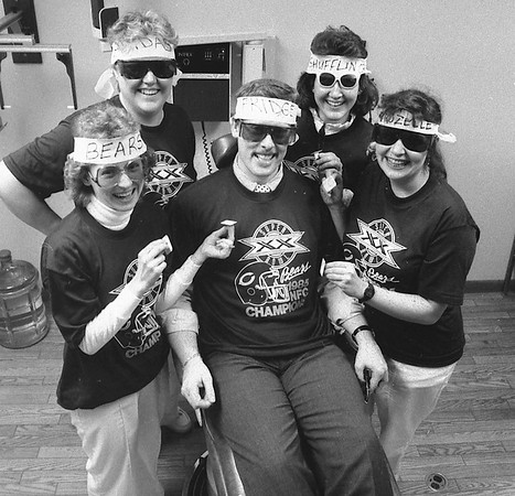 Jan. 24, 1986<br /> Dunlap dentist Dr. Michael Bigler and his staff had fun with the Chicago Bears this week, wearing headbands, sunglasses and T-shirts Thursday to show their support of the team, which will play the New England Patriots in Sunday's SuperBowl. Standing around the dentist are, from left, Susie Gipson, Lisa Adams, Teri Schoen and Mary Ann Filley. <br /> Goshen News photo by Mike Philley.